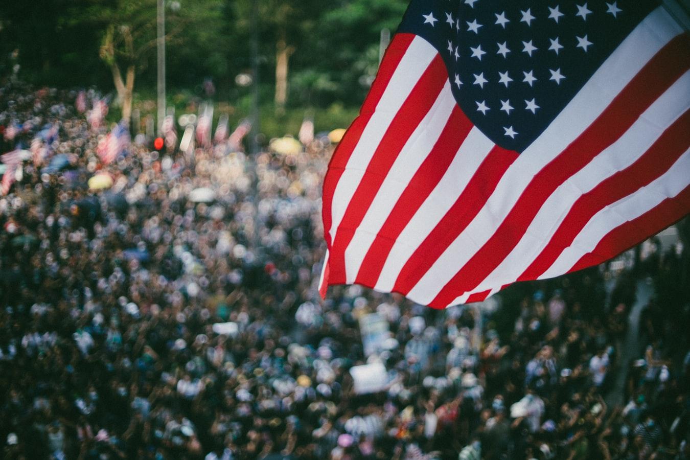 Drapeau américain flottant au dessus d'une foule.