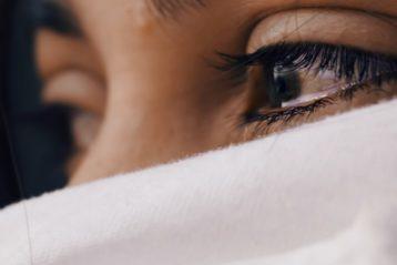 Une jeune femme avec un voile, les yeux embués de larmes.